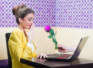 Man offering a rose to a beautiful woman over laptop screen